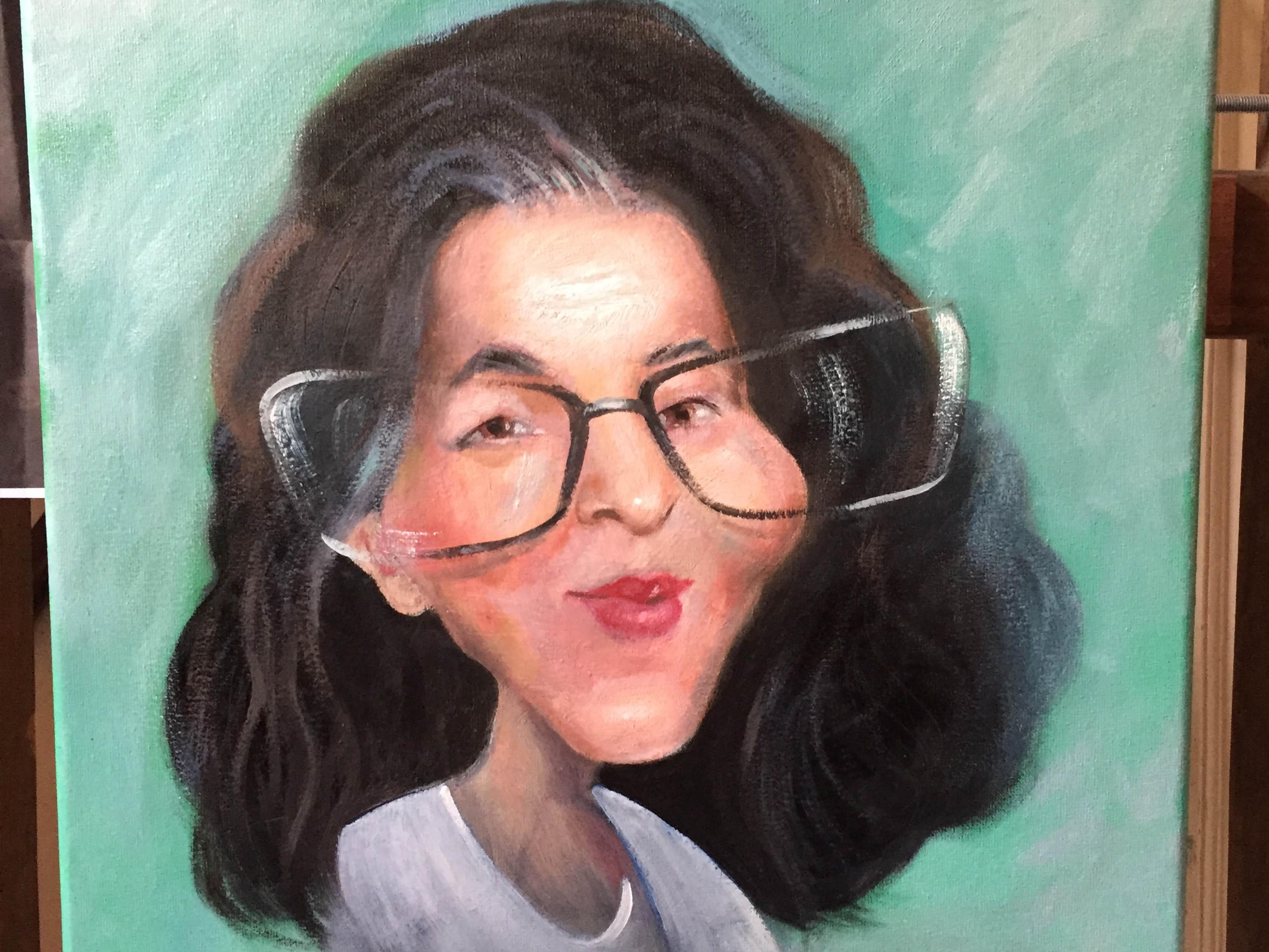 Caricature sur toile. Peinture à l'huile. Caricature à l'huile d'une femme en lunettes avec des cheveux noir et en boucle. Réalisation d'une caricature sur toile en couleur